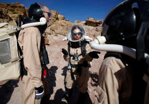 Melissa Battler (C), a geologist and commander of Crew 125 EuroMoonMars B mission, talks to members of the crew about collecting geologic samples for study at the Mars Desert Research Station (MDRS) in the Utah desert March 2, 2013. The MDRS aims to investigate the feasibility of a human exploration of Mars and uses the Utah desert's Mars-like terrain to simulate working conditions on the red planet. Scientists, students and enthusiasts work together developing field tactics and studying the terrain. All outdoor exploration is done wearing simulated spacesuits and carrying air supply packs and crews live together in a small communication base with limited amounts of electricity, food, oxygen and water. Everything needed to survive must be produced, fixed and replaced on site. Picture taken March 2, 2013. REUTERS/Jim Urquhart (UNITED STATES - Tags: SCIENCE TECHNOLOGY SOCIETY ENVIRONMENT) ATTENTION EDITORS: PICTURE 15 OF 31 FOR PACKAGE 'MARS IN THE DESERT' SEARCH 'JIM MARS' FOR ALL IMAGES ORG XMIT: PXP15
